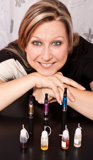 a women sitting and showing mix of e-liquids